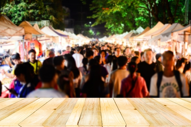 Light brown wooden board table on front with blurry defocused crowd of anonymous walking shopping on night market.