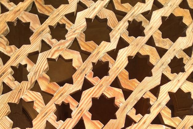 カットされた形の装飾品が付いている薄茶色の木製の格子