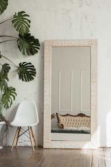 Light brown wooden mirror with ethnic pattern in a bright room with white walls