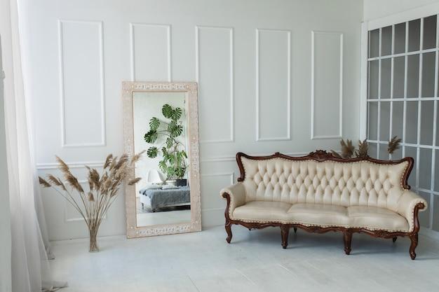 흰 벽이있는 밝은 방에 에스닉 무늬가있는 밝은 갈색 나무 거울