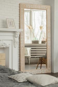白い壁の明るい部屋でエスニックパターンの明るい茶色の木製ミラー