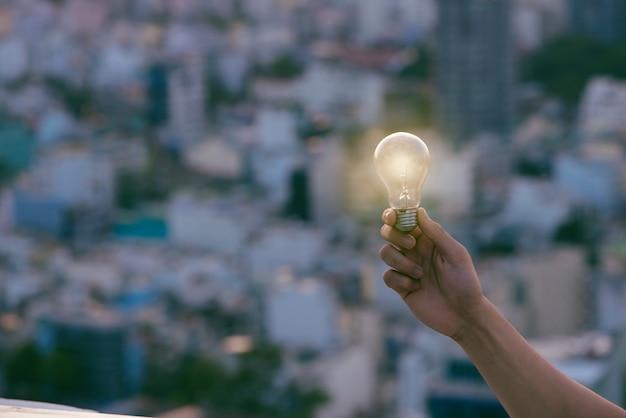 일몰 도시 주택 위에 전구입니다. 도시, 도시, 도시 밤 생활에서 남자의 대체 태양 에너지에 전구 투명 램프. 기호, 비즈니스 새로운 창의적인 아이디어의 개념입니다. 에코 에너지 절약