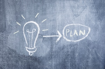 Light bulb and arrow pointing toward plan drawn on the chalkboard