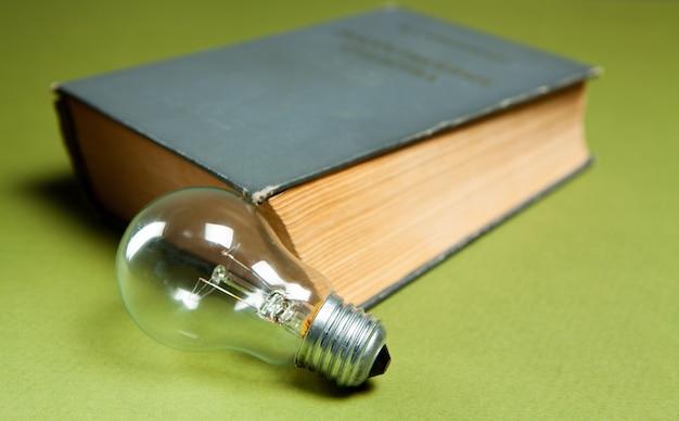 電球とテーブルの上の本。新しいアイデア