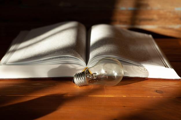 전구 및 테이블에 책. 새로운 아이디어