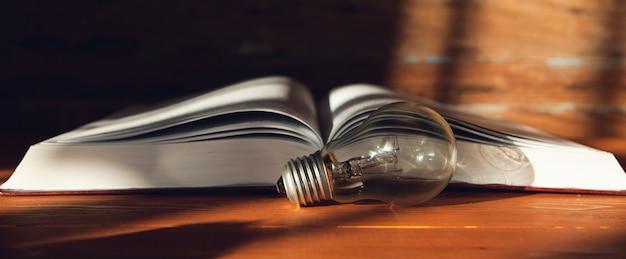 전구 및 테이블에 책입니다. 새로운 아이디어