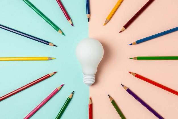 Лампочка и цветной карандаш на синем и розовом фоне
