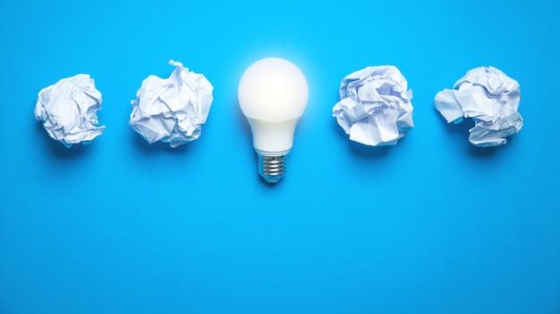 Лампочка и скомканные бумаги на синем фоне