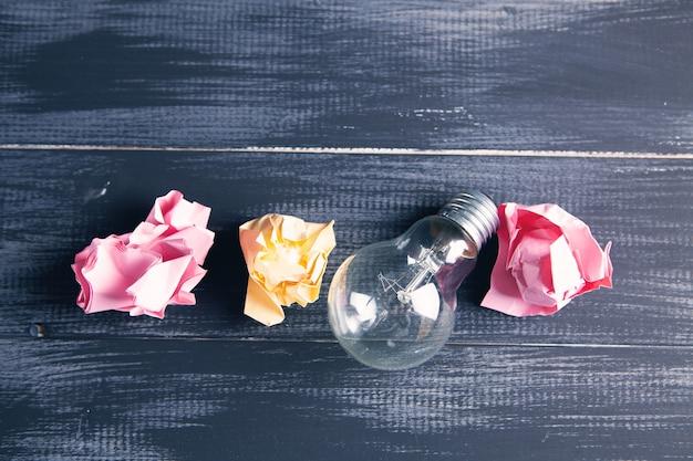 電球とテーブルの上のしわくちゃの紙