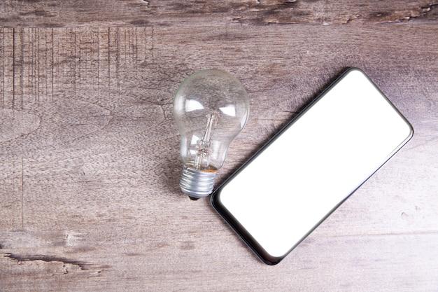테이블에 전구와 스마트폰