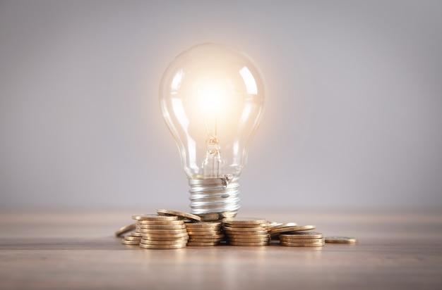 電球と机の上のコインのスタック。エネルギーとお金の節約