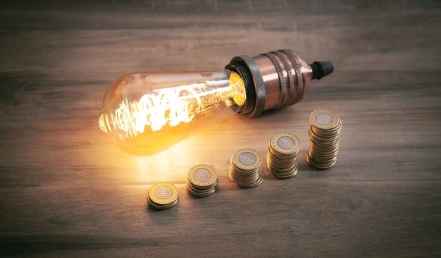 木製の背景に電球とコインのスタック。エネルギーとお金の節約