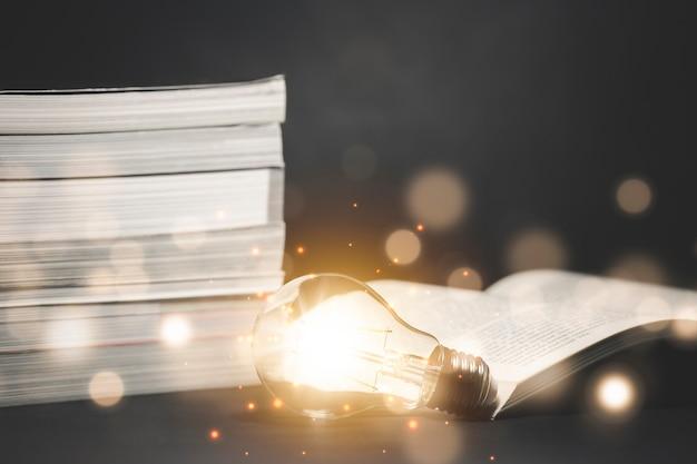 Лампочка и старинная книга с размытыми огнями