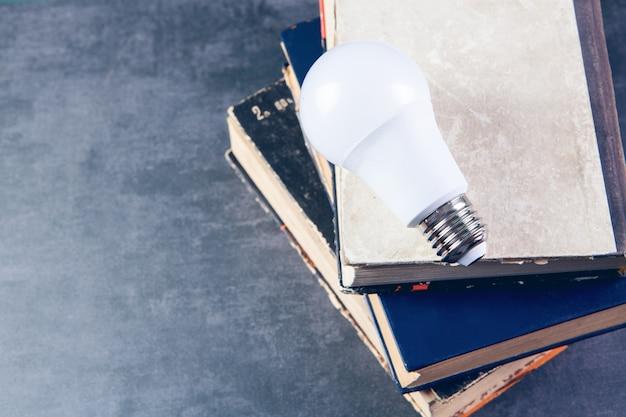 Light bulb on books on table