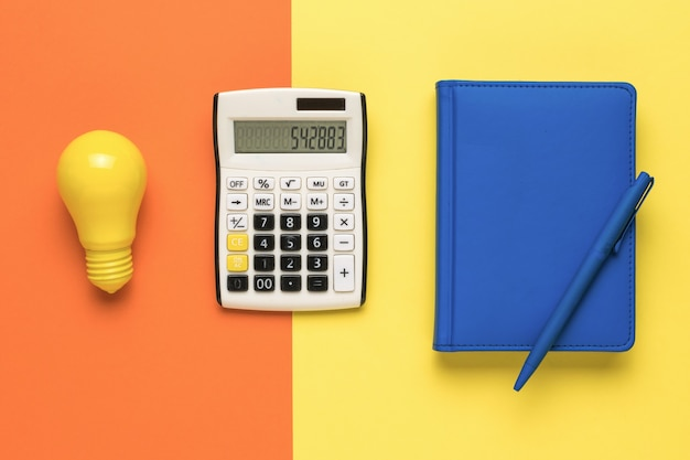 A light bulb, a calculator and a notebook on a two-color background.