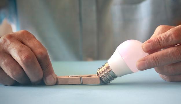 洗濯バサミで電球を捕まえた。省エネコンセプト。 sopaceをコピーします。セレクティブフォーカス。