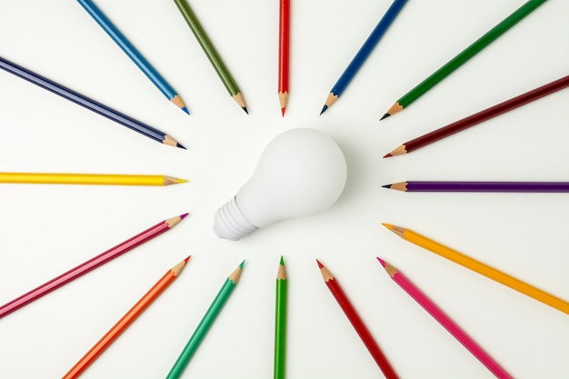 Light bulb and colored pencil on white background