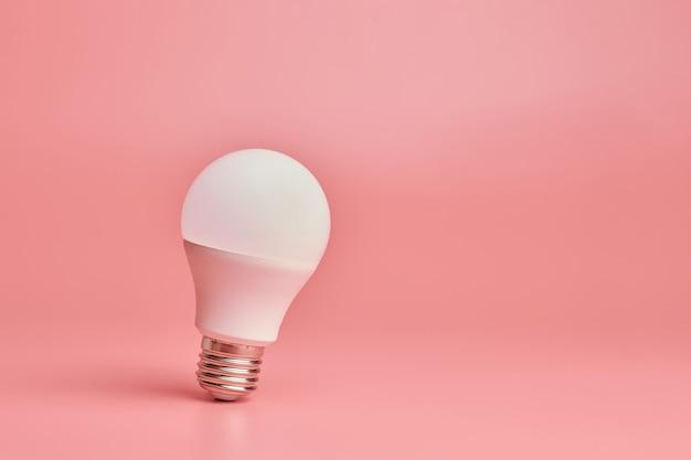 전구, 복사 공간. 에너지 절약 최소한의 아이디어 개념 핑크 배경입니다.
