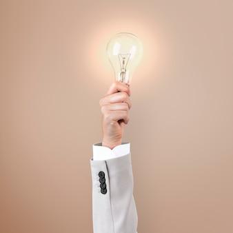 手で持つ電球の創造的なビジネスアイデアのシンボル