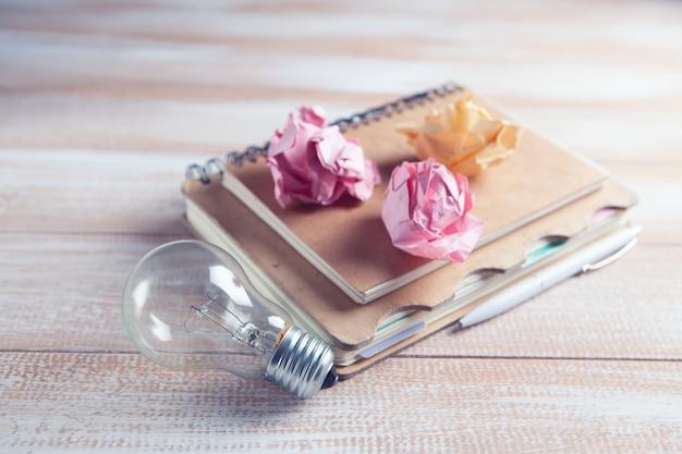 테이블에 전구, 구겨진 종이 및 메모장