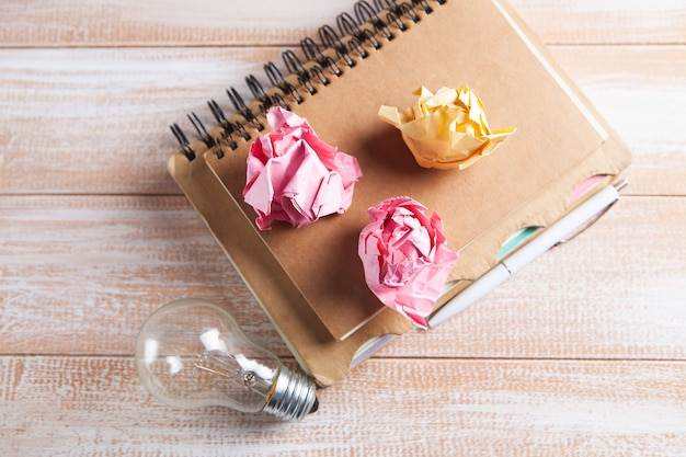 Light bulb, crumpled papers and notepad on the table