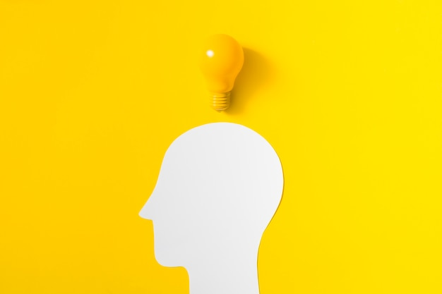 Light bulb over the cut out white human head on yellow background
