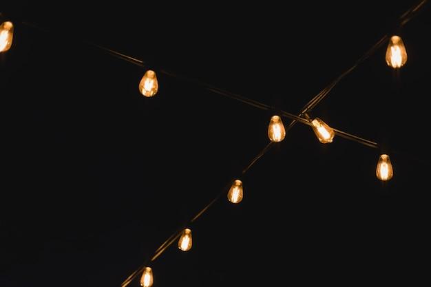 Декор лампочки на открытом воздухе. декоративные уличные гирлянды в ночное время. золотая светящаяся гирлянда на свадьбе