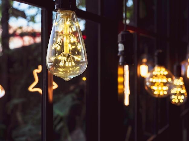 Украшение лампочки в кафе. многие светодиодные лампы в стиле ретро светятся возле стеклянного окна.