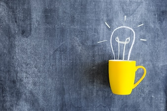 Light bulb drawn over the yellow mug on chalkboard