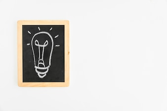 Light bulb drawn with chalk on slate over the white background