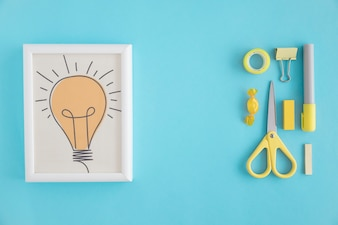 Light bulb frame and stationery with yellow chocolate on blue background