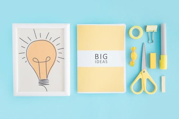 電球フレーム;青い背景に大きなアイデアブックと文房具