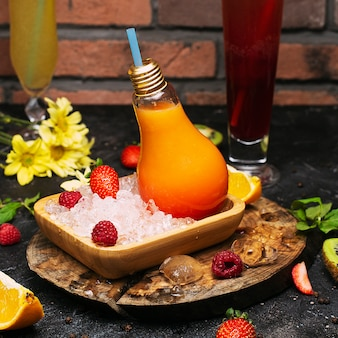 Light bulb glass bottles with fresh orange tropical fruits juice on plate with ices cubes and strawbesrries. vacation relaxation detox cleansing wellness
