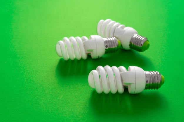 Light bulb on green paper background close up