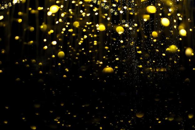 Light bulb hanging a chandelier, illuminating a small, beautiful yellow gold bokeh