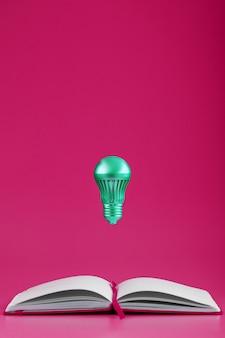 Лампочка нависает над открытыми страницами пустой тетради на розовом фоне