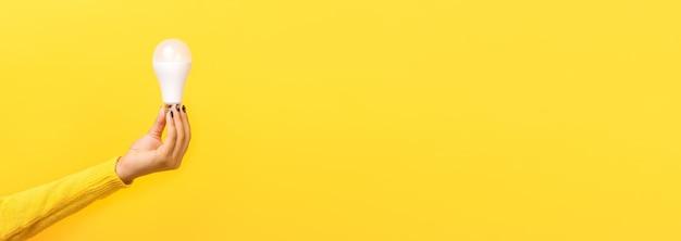 노란색 배경 위에 손에 전구