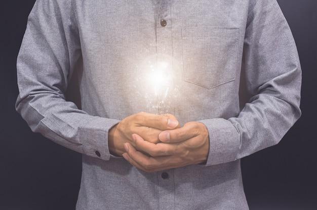 Лампочка в человеческих руках, концепция новой идеи