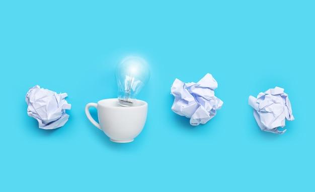 青の背景に白のしわくちゃの紙のボールと白いカップの電球。アイデアと創造的思考の概念。