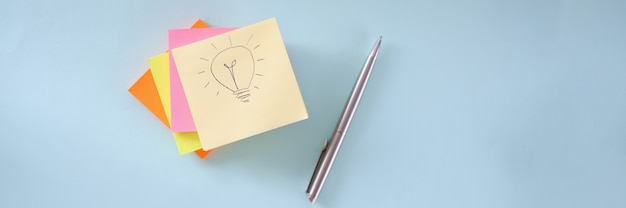 Light bulb is drawing on piece of paper many colorful stickers and ballpoint pen lying on table