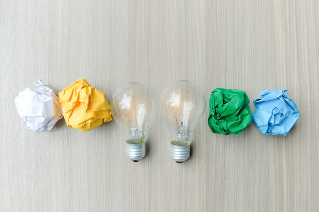 Light bulb or lamp with colorful crumpled paper on wooden table