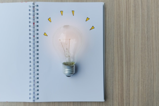 Light bulb or lamp with notebook on wooden table.