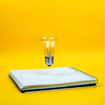 新しいアイデアの概念としてのノートブックの上を浮上している電球