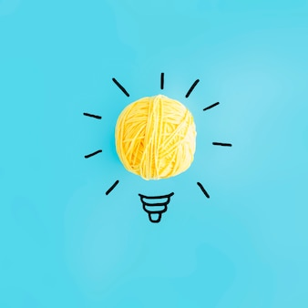 Light bulb made with yellow ball of yarn on blue backdrop
