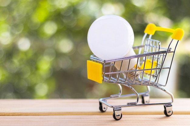 Light bulb in mini shopping cart against blurred natural green background.