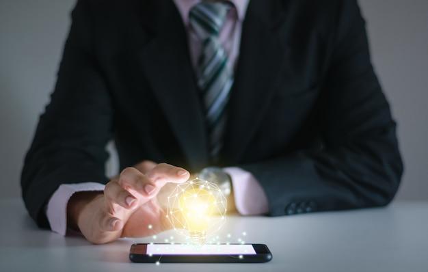 電球の革新的な技術コンセプトを持つ新しいアイデア、ビジネスマンの手