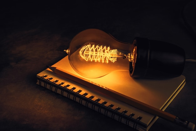 Light bulb on a notebook with pencil, inspiration and education background concept.