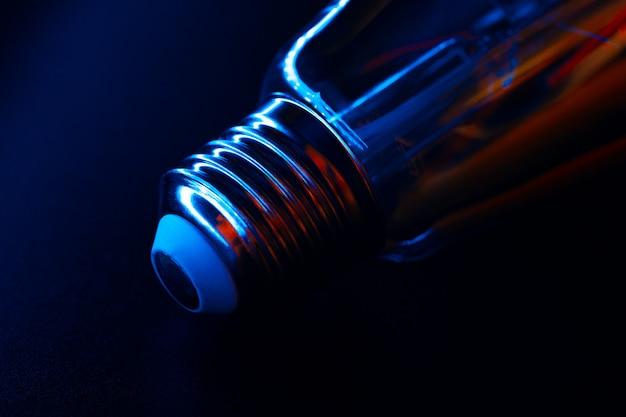 Лампочка на черном неоновом цвете, крупный план