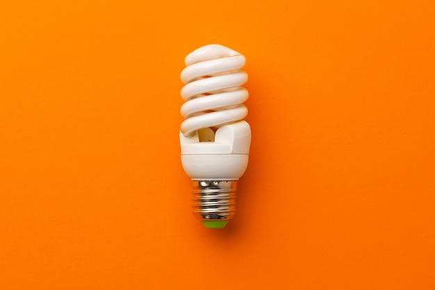 明るいオレンジ色の背景の上面図の電球