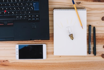 Light bulb on notebook near technologies